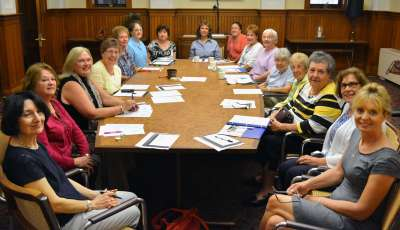 Auxiliary women sitting around a large conference table holding a meeting.
