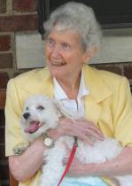 Sister Silveria holding Buster, a white Maltese therapy dog.