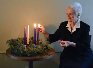 Sister Mary Ann Thimons lighting a candle for the second week of Advent.