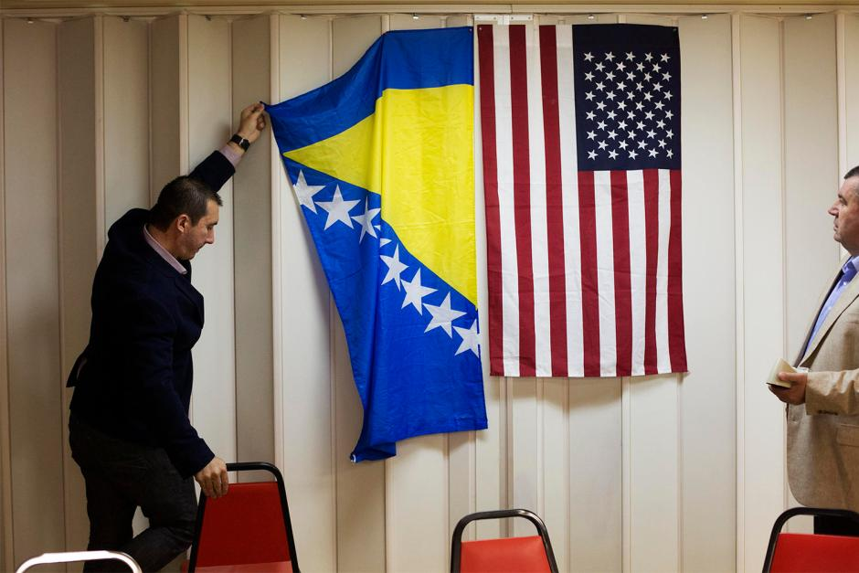 Akif Cogo, with St. Louis Bosnians, hangs the flag of Bosnia and Herzegovina alongside an American flag to serve as a backdrop for a press statement at the Bosnian Chamber of Commerce on Gravois Avenue following the sentencing of Radovan Karadzic by the United Nations' International Criminal Tribunal for the former Yugoslavia.