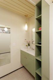the-master-bathroom-features-updated-fixtures-and-colorful-cabinetry