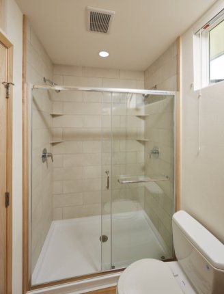 the-escape-design-team-outfitted-the-main-bathroom-which-connects-to-the-bedroom-with-a-large-shower-that-features-glass-doors