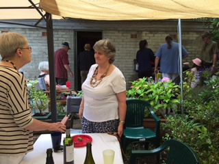 Jennie and Kathy deep in conversation - men at work at the BBQ behind!