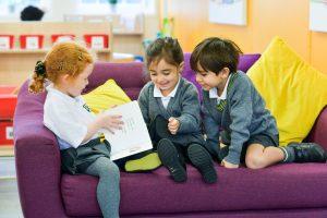 Nursery pupils reading a book on a sofa