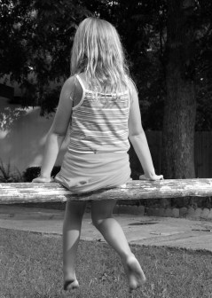 Black and white image of a young girl on a split rail fence.