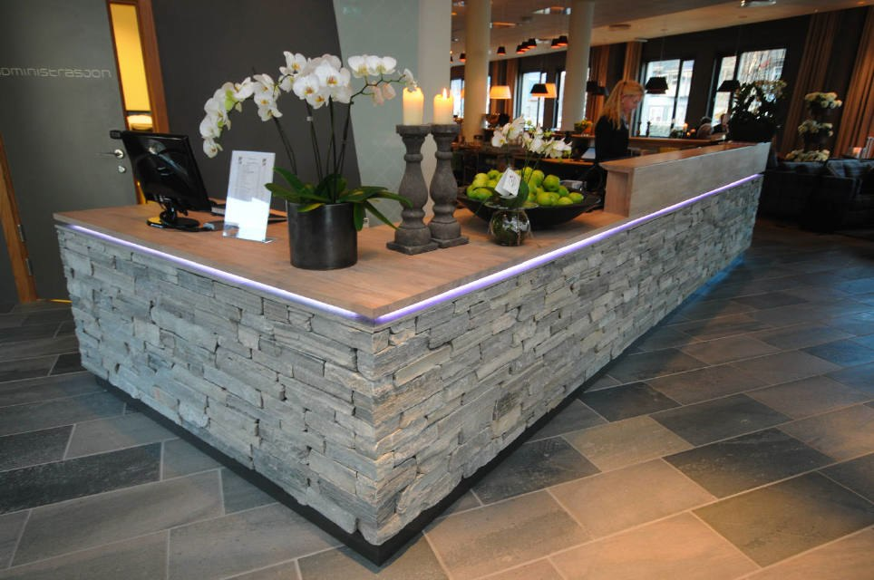 on the interior of the building the slate dry wall is a central theme as at the reception desk and fireplace in the lounge