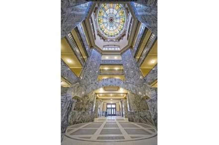 Das Innere erschließt sich über eine Rotunde, die 6 Stockwerke in die Höhe reicht. Oben trägt sie ein Glasmosaik.