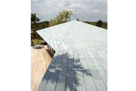 O teto é revestido com placas de ardósia, de modo que o material tem um fluxo contínuo em todo prédio. De duas sacadas é possível ver o teto.