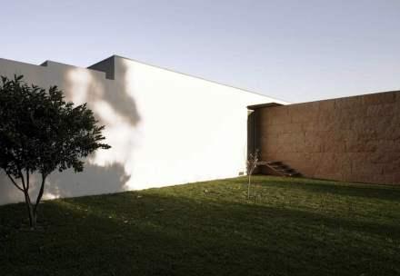 Nos fundos, ela divide a área da piscina da entrada para garagem, jardim e escritório.