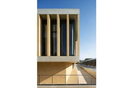 Auch im Äußeren des Neubaus wurde der Kalkstein auf markante Art und Weise eingesetzt, dort für senkrechte Pfeiler vor den Fenstern.