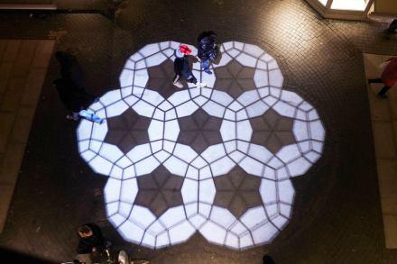 Además de esta geometría, digamos, fija, hay otra en movimiento: un proyector ilumina desde arriba la pequeña plaza.