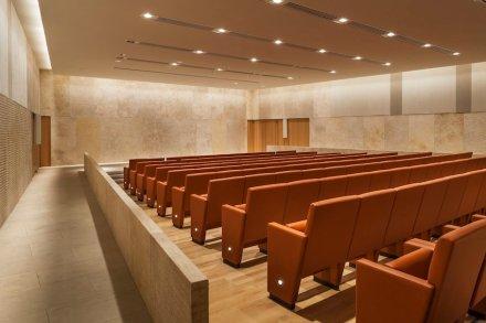 Im Auditorium mit 150 Sitzplätzen findet man wieder die goldene Variante des Steins. Aus akustischen und dekorativen Gründen sind Flächen aus Textilien beziehungsweise aus Holz zwischen die Steinplatten eingefügt.