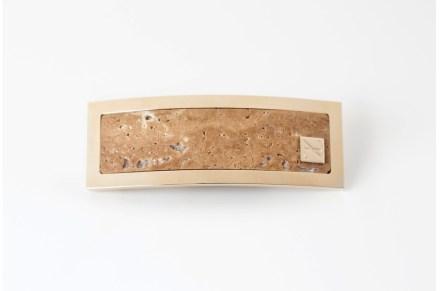 Zu ihrer aktuellen Kollektion zählen Gürtelschnallen. Hier findet man den Travertin Classico im Goldrahmen mit Sara Devotis Markenzeichen..,