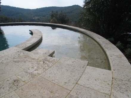 Piscina redonda de travertino Becagli en la Toscana.