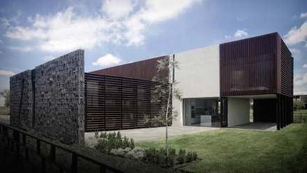 En el exterior, llaman la atención las paredes de hormigón con superficie corrugada (izq).