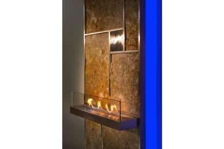 """""""Juwall"""": Wärmewand mit Elektroheizung dahinter, bei der der Stein als Wärmespeicher wirkt. Mit Flammenzeile oder Handttuchablage."""