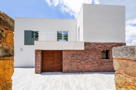 Als Gegensatz dazu ist das Erdgeschoss des Hauses mit handgefertigtem Backstein verkleidet, dessen rote Farbe auch nicht zu übersehen ist.