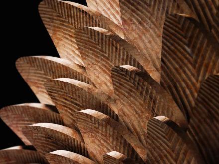 "Digital Lithic Design: ""Pavo"". The huge stone fan inspired by the bird feathers was created by managing the repetition of elements using 3D software. The special features of the work lies in the achievement of surface texture directly derived from the tool's machining path controlled individually for each single item to become an integral and distinguishing aspect of the project. Design: Raffaello Galiotto, produced by Donatoni."