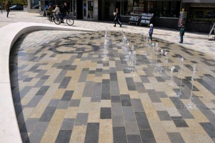 The fountain on the Elben Place at the foot of the historic city center demonstrates how the color of stone changes when wet. Gray tones are predominant around the seating. Photo: Besco