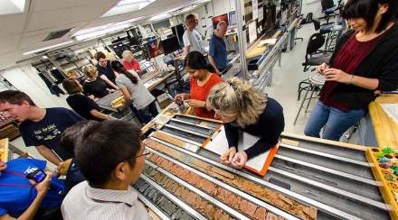 Scientists examine the halves of a freshly split core. Photo: Tim Fulton, IODP-JRSO