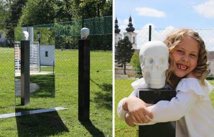 """Erich Trummer, """"Der liebe Tod und ich"""": im Hochbarock kommen auf den Friedhöfen Symbole für die Vergänglichkeit (vanitas) in Mode. Besonders beliebt ist der Totenkopf - hier in Marmor gefertigt und auf eine Stele gestellt. Besucher können sich daneben stellen und sich (und ihre unausweichliche Zukunft) in einem Spiegel betrachten."""