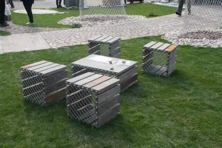 Seating group for which narrow strips of stone are used holding together a stainless-steel mesh.