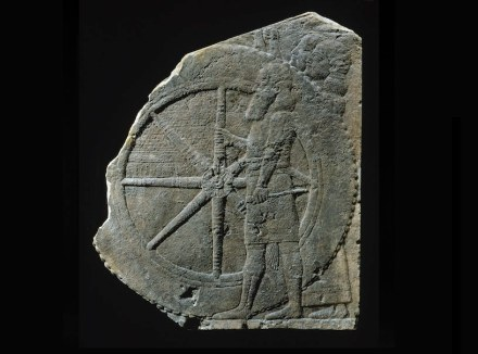 Fragment of a relief with a chariot, limestone, h. 55 cm, l. 46.5 cm.; 7th century BC, found in Nineveh. This relief was found in the northern Assyrian palace of Nineveh. It displays a bearded soldier grasping one of the large wheels of the royal chariot. The two men standing behind the wheel are holding a screen. Photo and collection of © Musée du Louvre, Paris