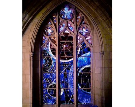"The ""Space Window"" in Washington's National Cathedral, designed by artist Rodney Winfield, depicts whirling stars and orbiting planets in orange, red and white on a deep blue and green field. The moon rock, weighing only 7.18 grams was set later in the center. Photo: NASA"