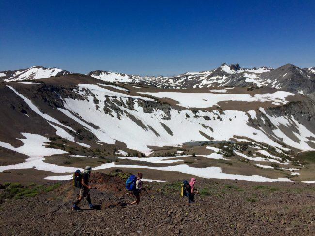 Beardoh Sweet Pea and Gazelle hiking above snow filled basins