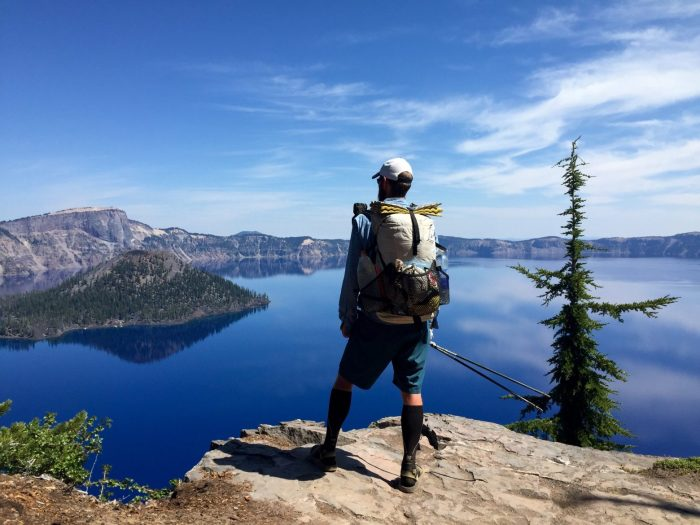 Mountain Man looking out over Crater Lake as it perfectly reflects the sky