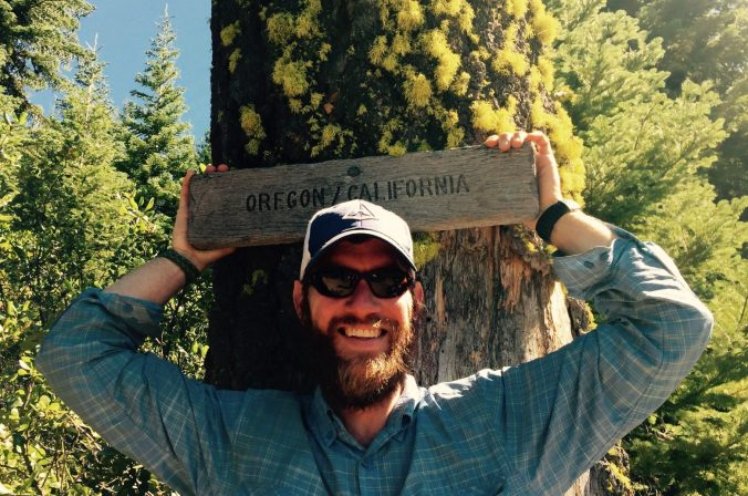 Mountain Man posing with the Oregon California border sign