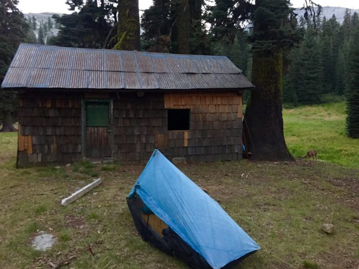 Tent pitched next to an abandoned ranger station in Marble Valley