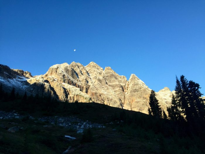 Blue sky behind jagged peak lit by the morning sun