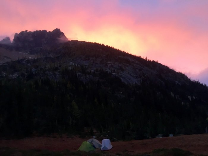 Pink and purple sky as sun rises over a peak in the North Cascades
