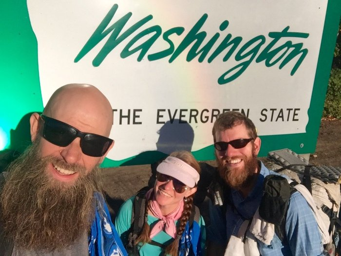 Beardoh Sweet Pea and Mountain Man in front of Welcome to Washington State sign