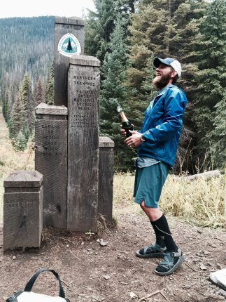Mountain Man popping champagne at the PCT Northern Terminus