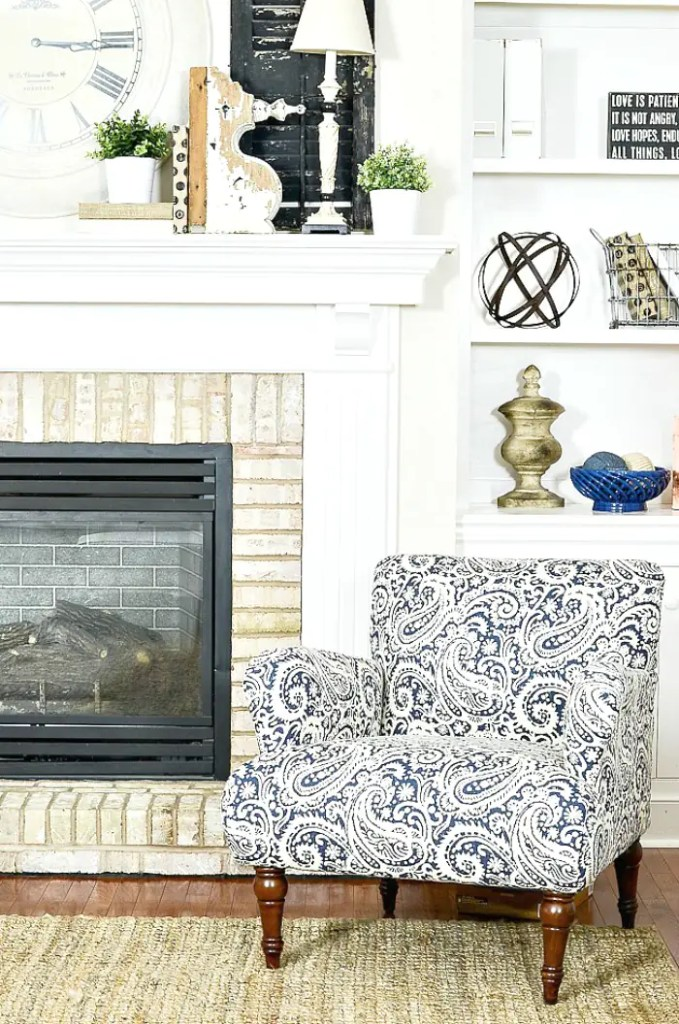 blue and white chair in front of the fireplace