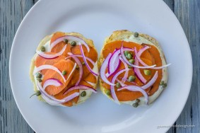 Bagel & Lox: Bagel, housemade garlic dill cream cheese & carrot lox, red onion, and capers