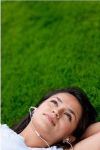 Listening to music is an activity mentioned in this month's blog. Shows a woman lying in grass with headset on.