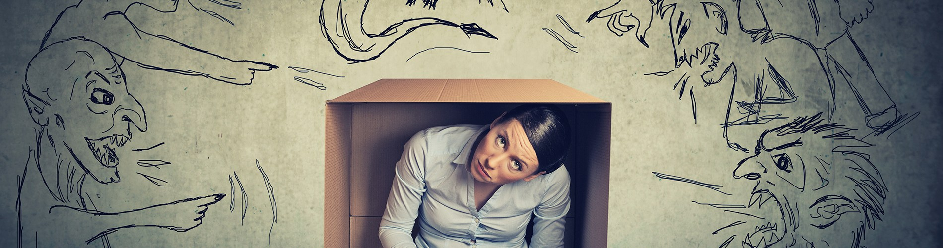 Woman typing, trapped in box by monstrous drawings
