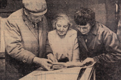 press cutting of 3 people viewing an exhibit