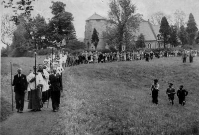 Black and white photo of the procession across church field, led by the Vicar