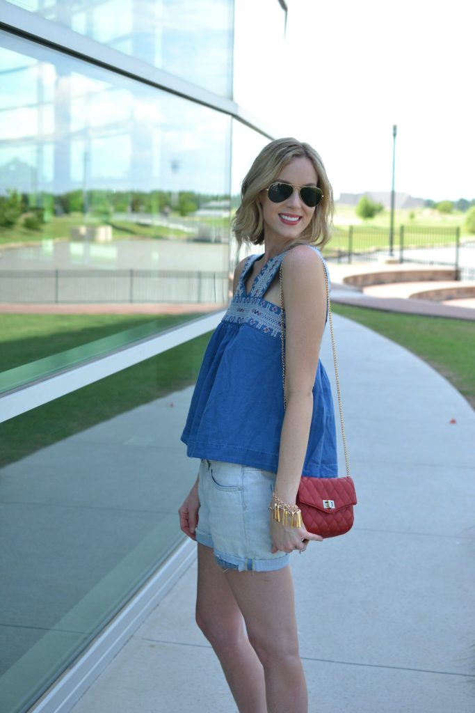 madewell denim top, jean shorts, red bag, fringe bracelet, aviators