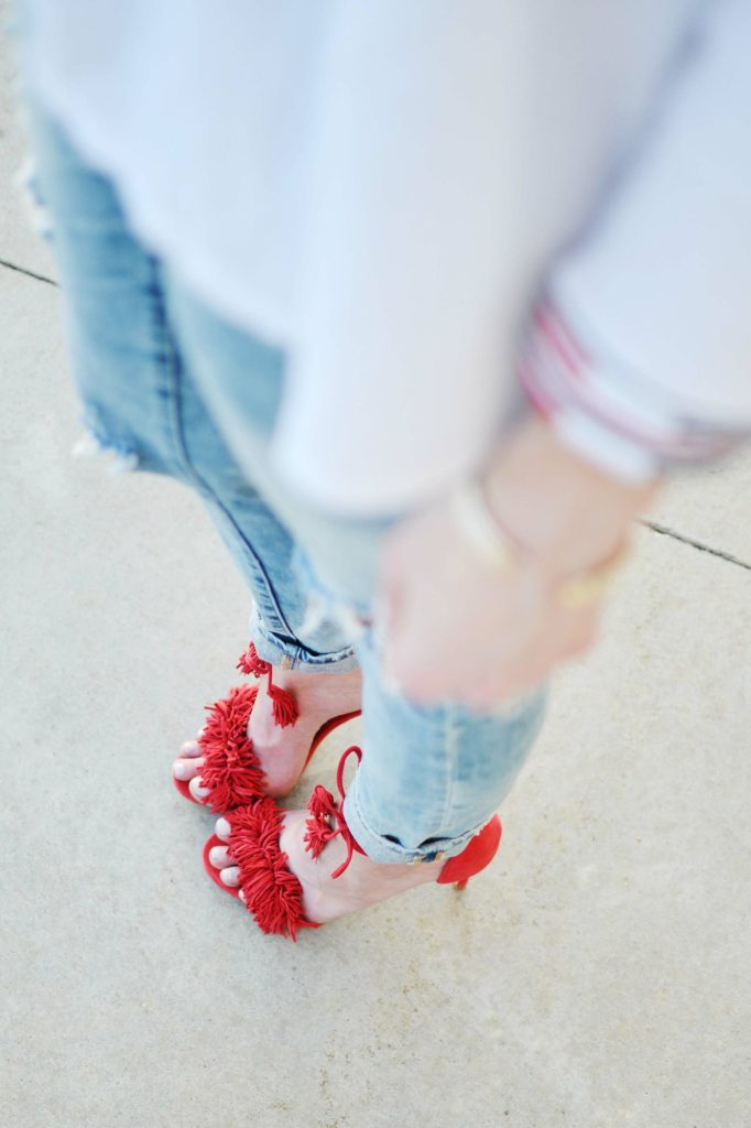 A sassy pair of red fringe shoes, fun embroidered top, and distressed jeans make for the perfect casual date night outfit.