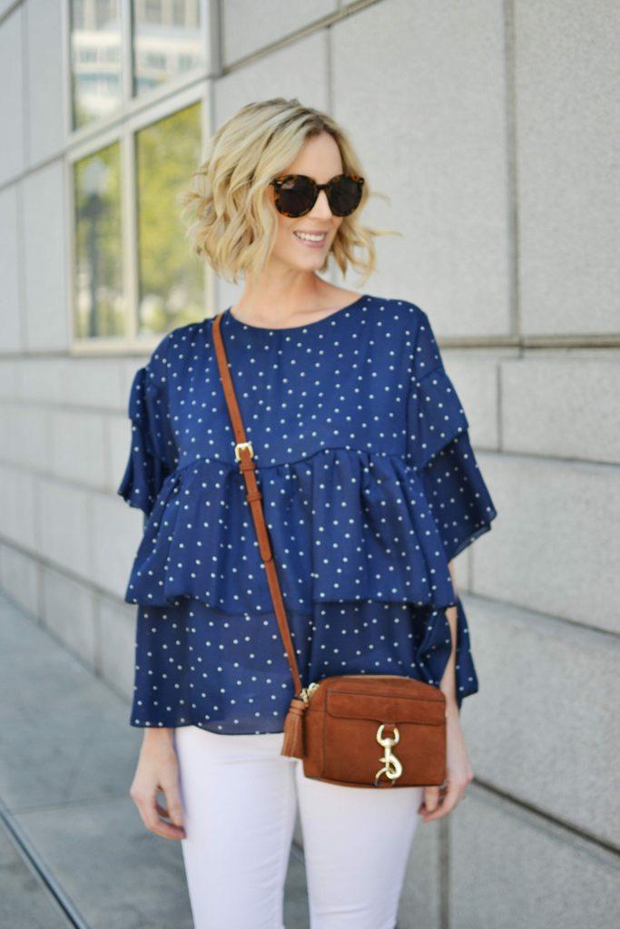 navy polka dot ruffle top, white jeans, tan Rebecca Minkoff bag