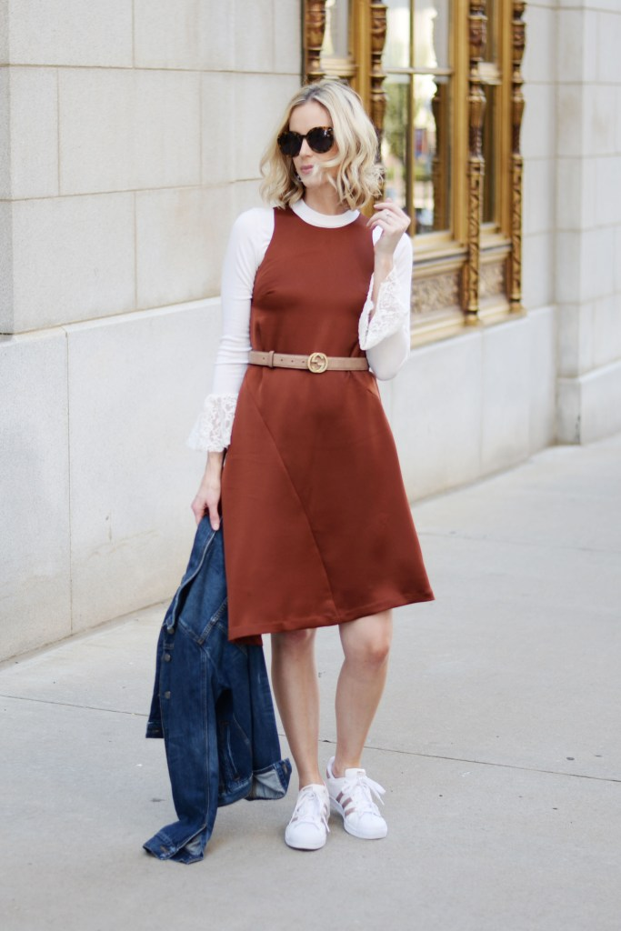 formal dress worn with tennis shoes and layered with top and jean jacket