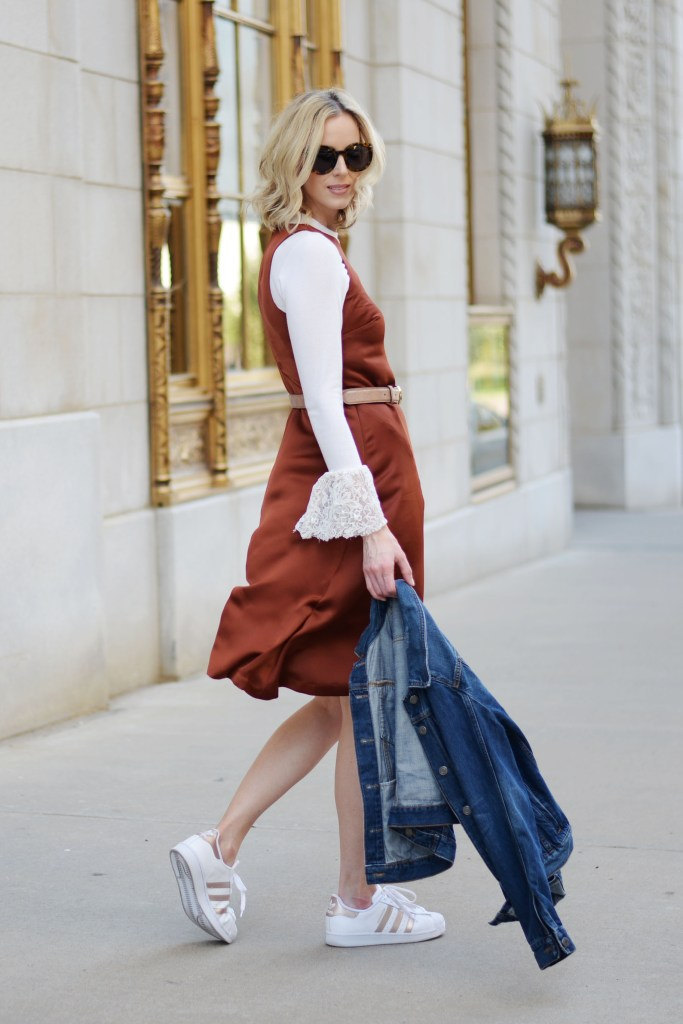 how to dress down a dressy dress, rust colored asymmetrical dress layered over a bell sleeve top with adidas superstars