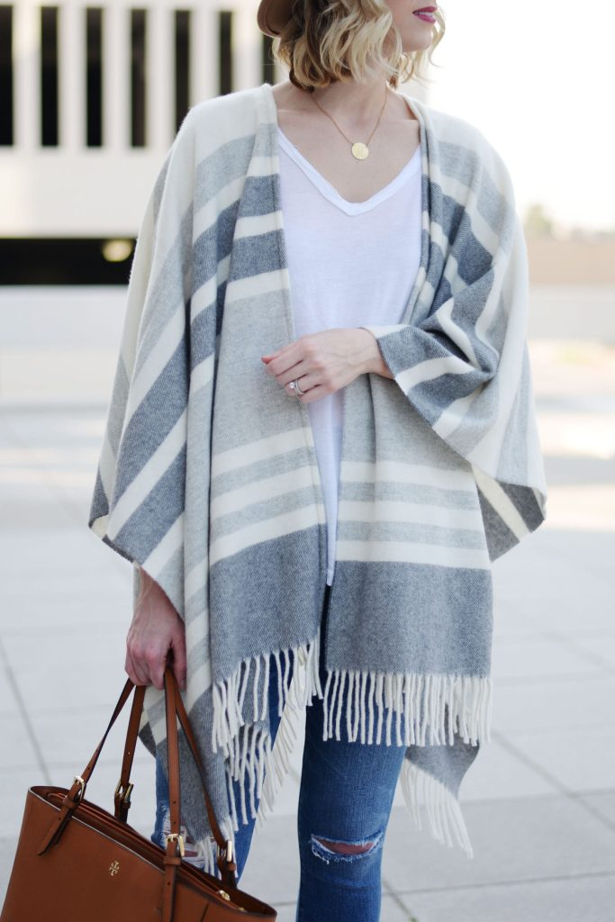 poncho styled over white t-shirt worn with jeans