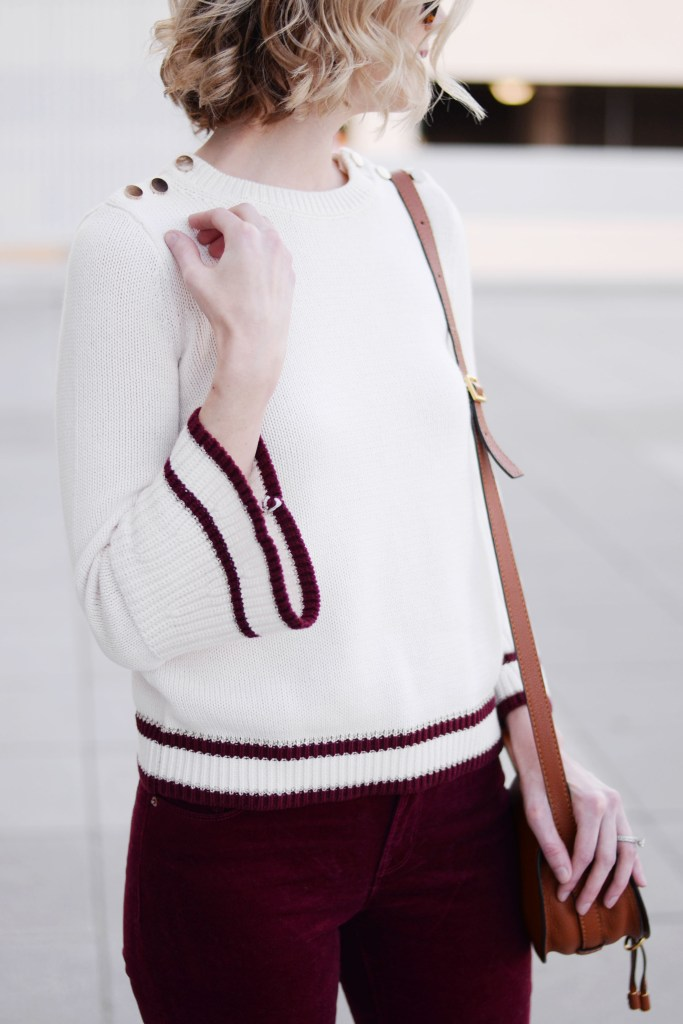 cream bell sleeve sweater with burgundy striped hem and gold shoulder button detail
