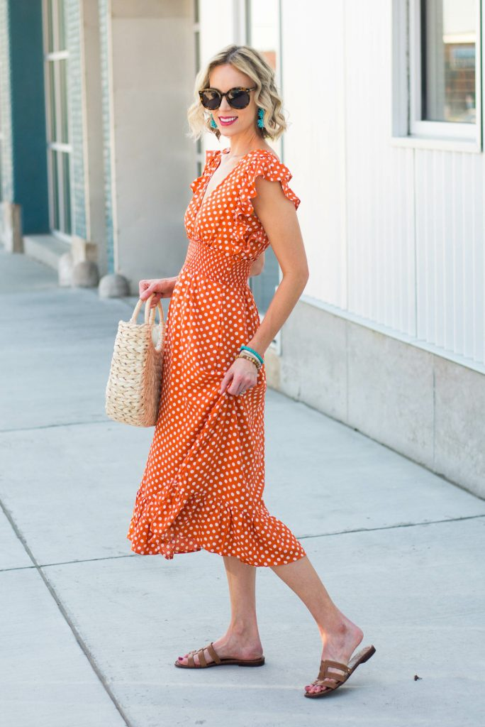 orange polka dot midi dress with ruffles, straw bag, turquoise accents